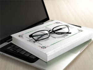 book and glasses laying on laptop