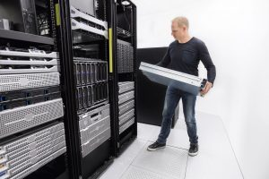 man in server room installing new hardware
