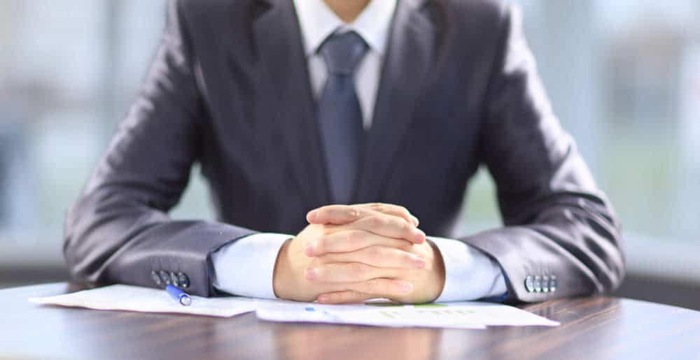 professionally dressed man with hands clasped over papers on table