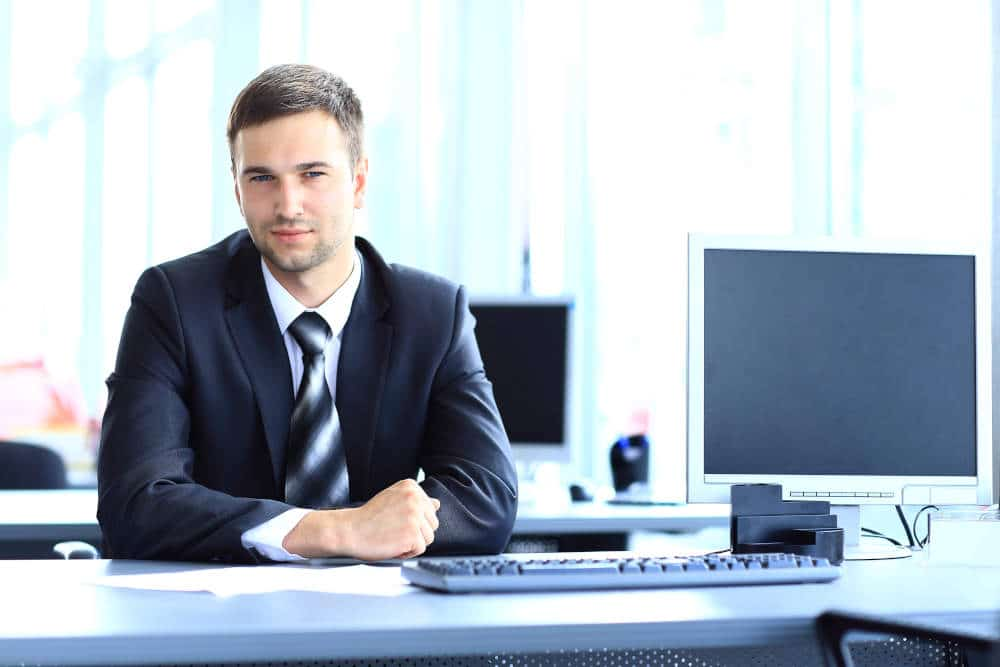 professionally dressed man sitting at desk