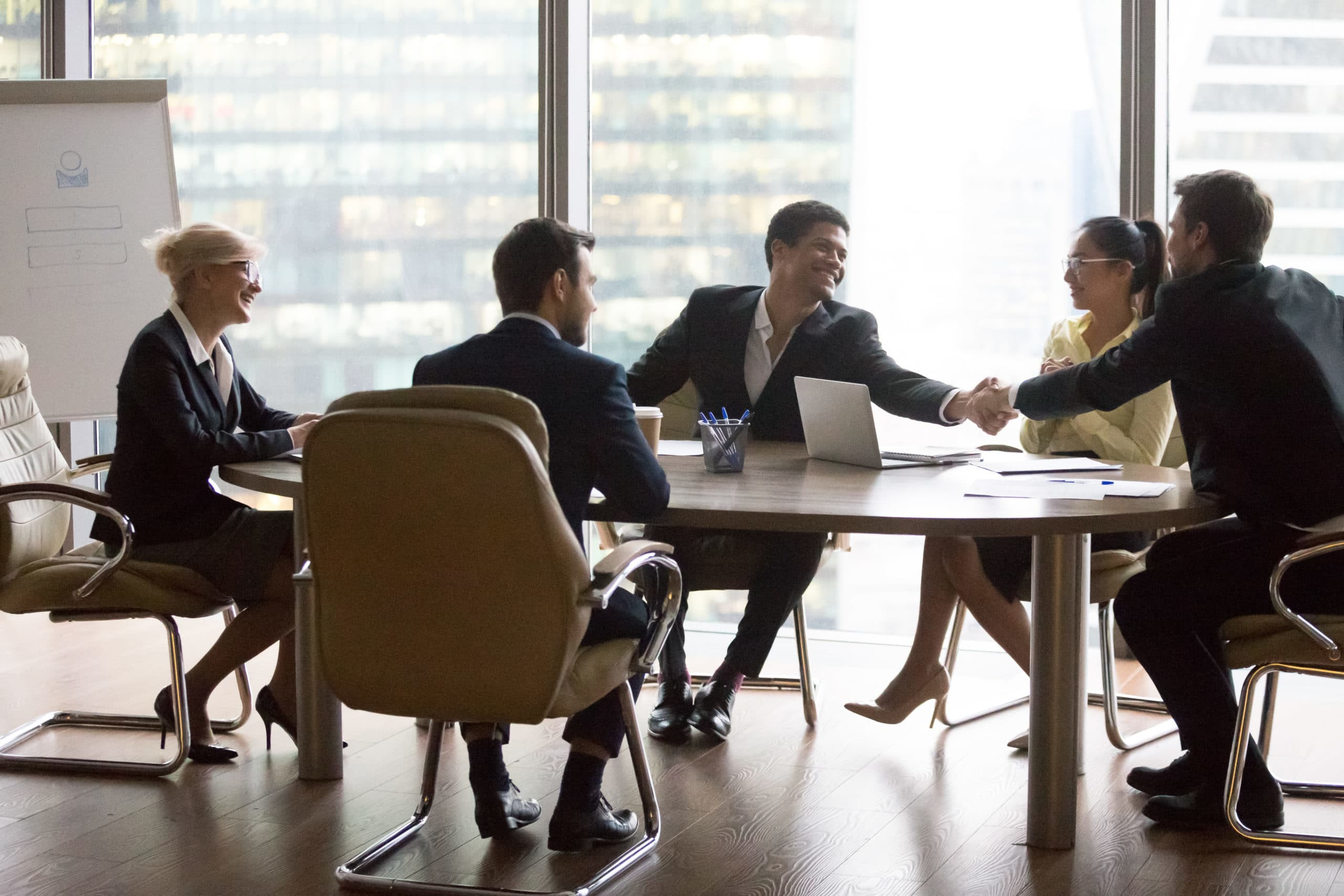 Smiling multiracial business people sitting at meeting