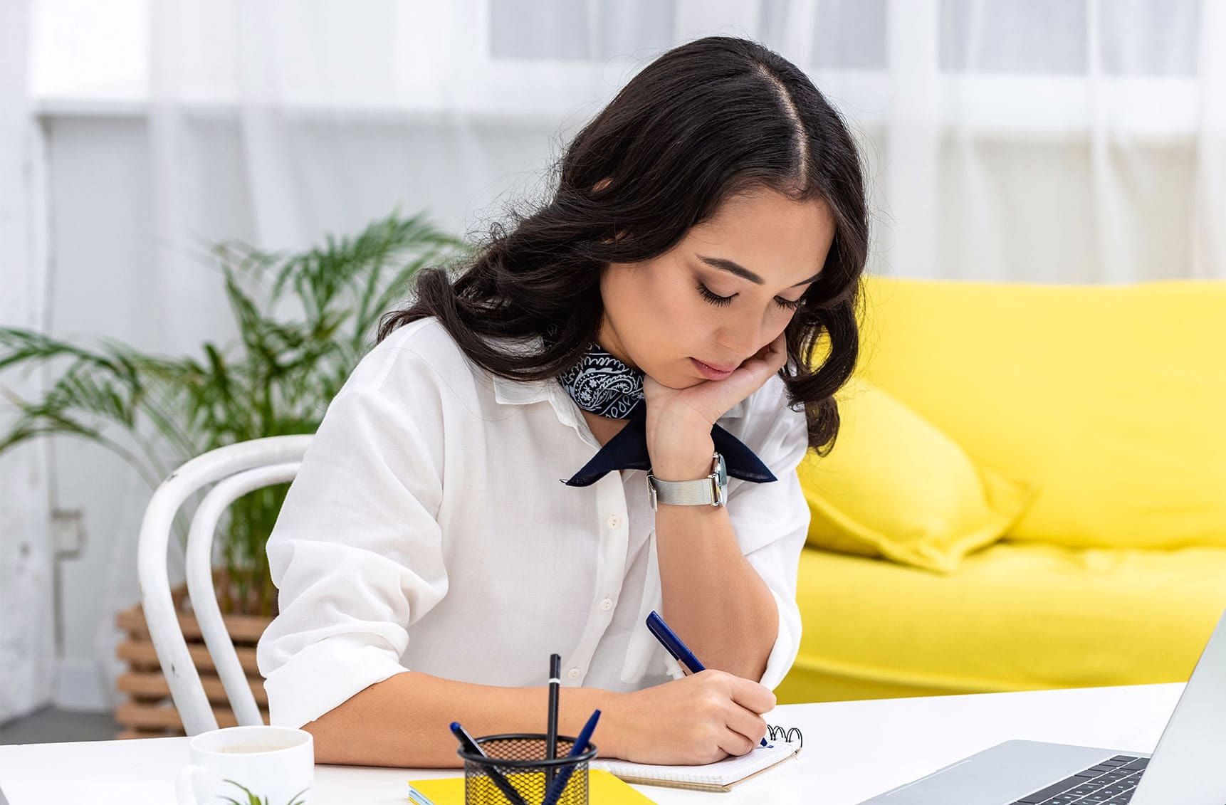 Professional woman sitting at desk writing in spiral notebook