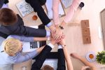 team of people with hands extended into middle of circle
