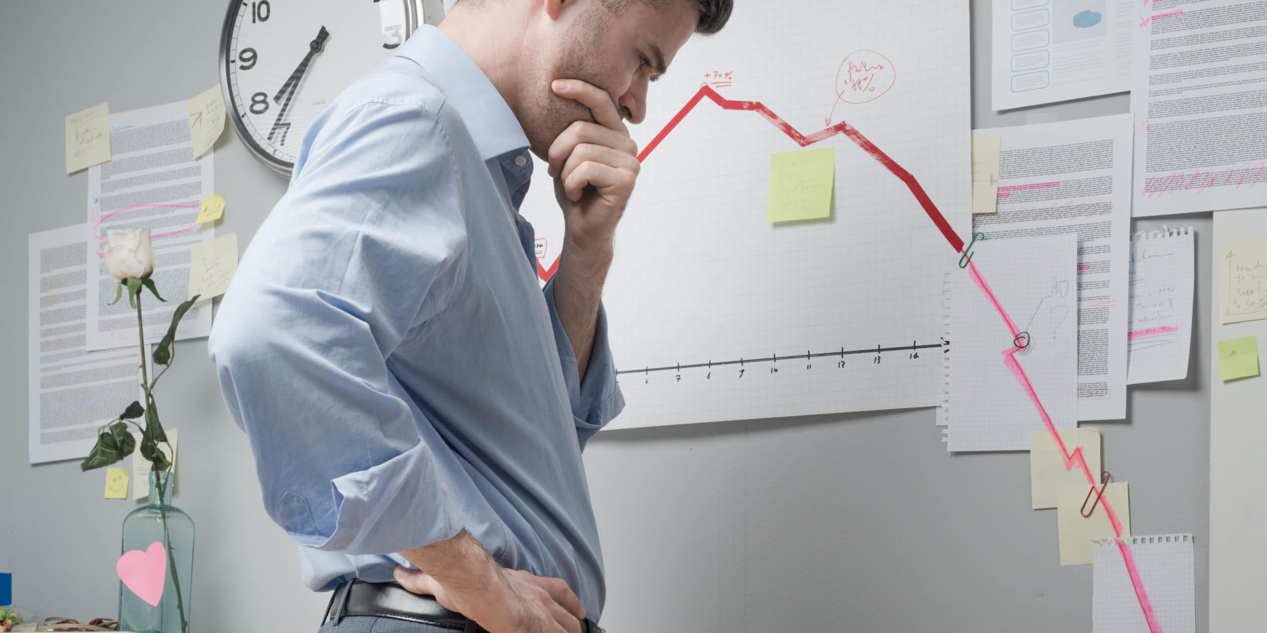 Concerned businessman at work looking at negative business chart with arrow going downwards.